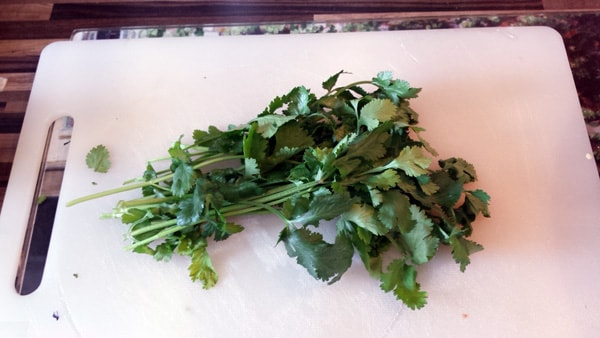 Half a bunch of fresh coriander on a chopping board
