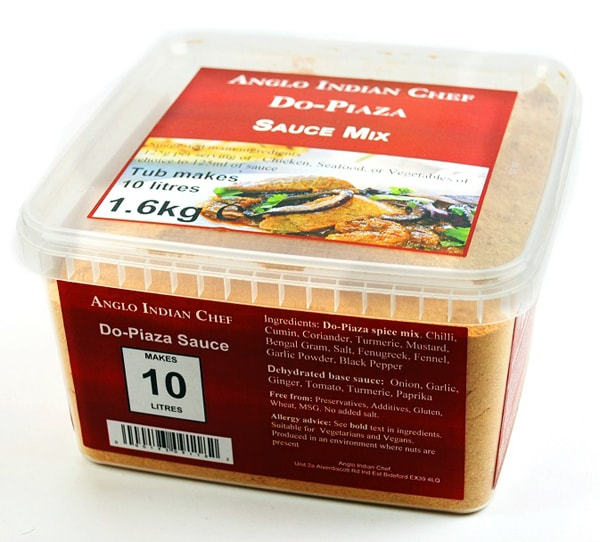 A square, lidded plastic tub with orange labels on all sides and a photo of a curry meal on the top, containing loose powder spice mix