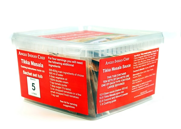 A plastic, lidded tub with orange labels on all sides and the top, containing Tikka Masala catering sachet sets.